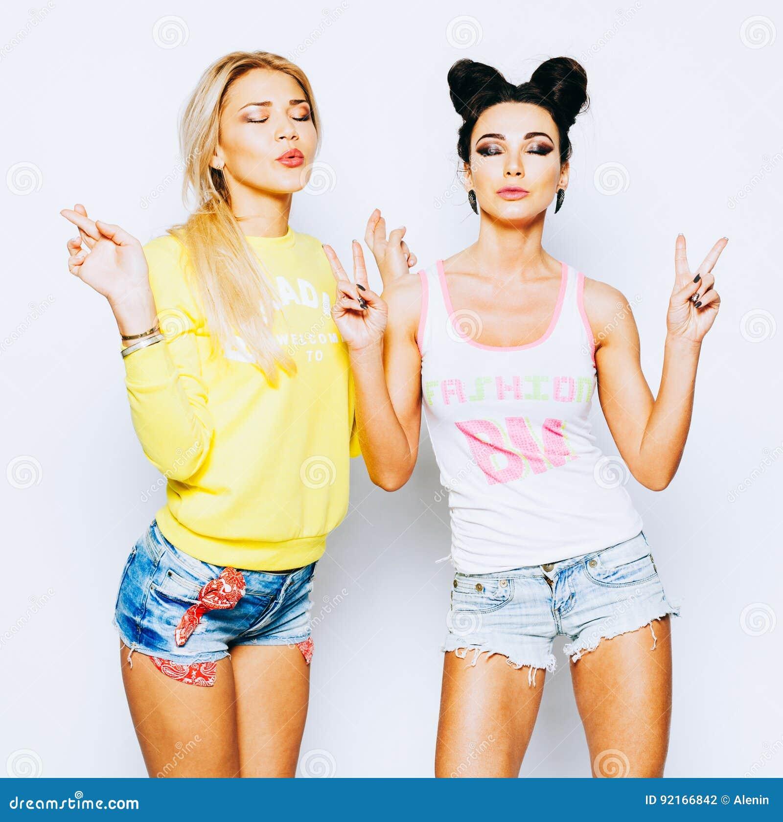 Dos muchachas en los equipos brillantes de la moda, pantalones cortos Medite relaxedly con los ojos cerrados que muestran una mue