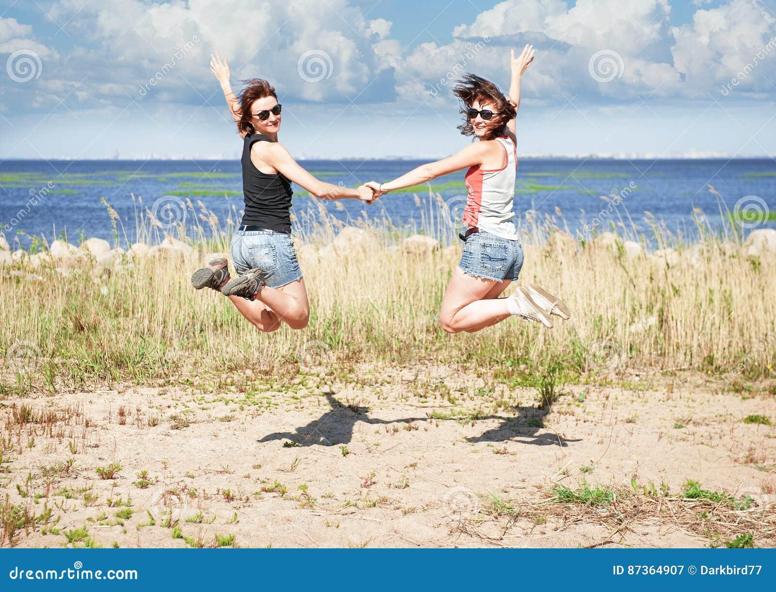 Dos muchachas felices que saltan en la playa en verano