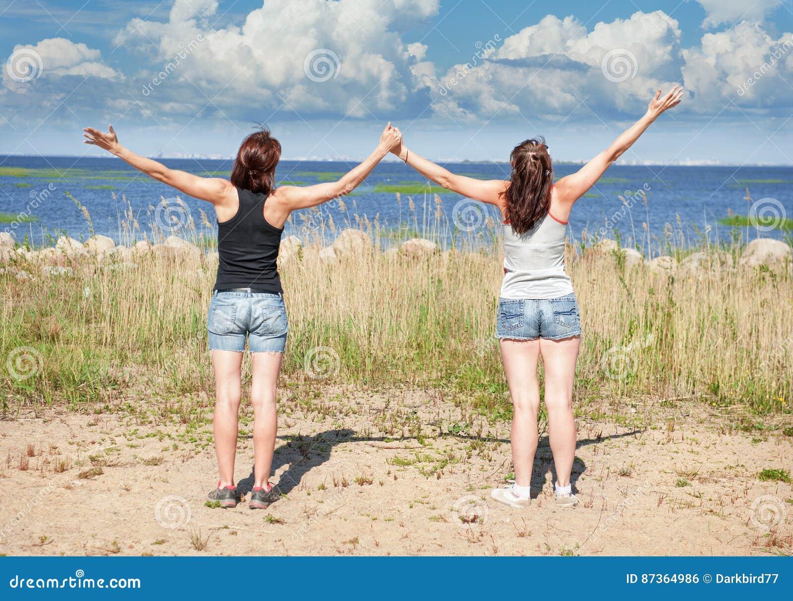 Dos muchachas felices que se colocan en la playa en verano