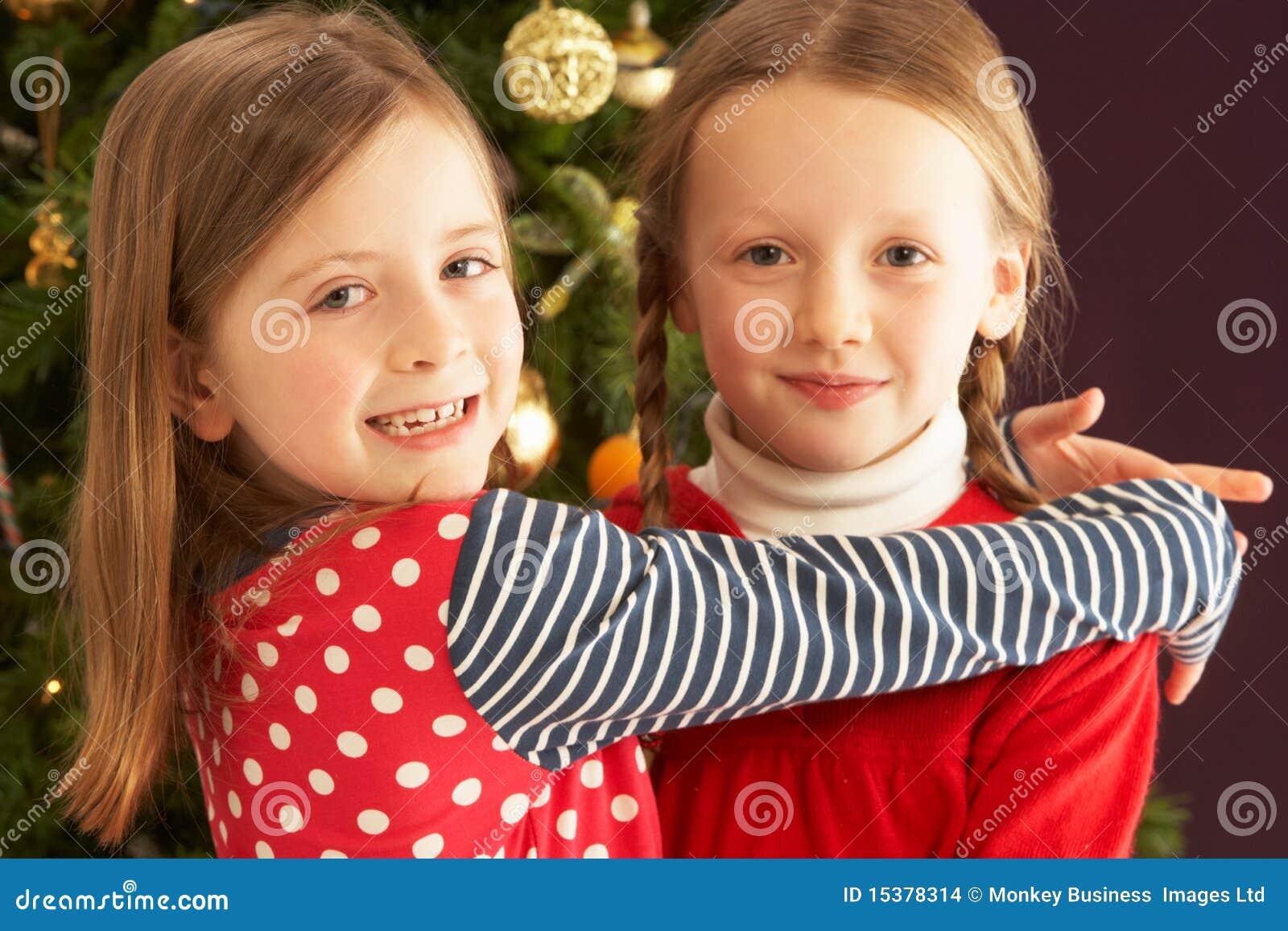 Dos muchachas que abrazan delante del árbol de navidad