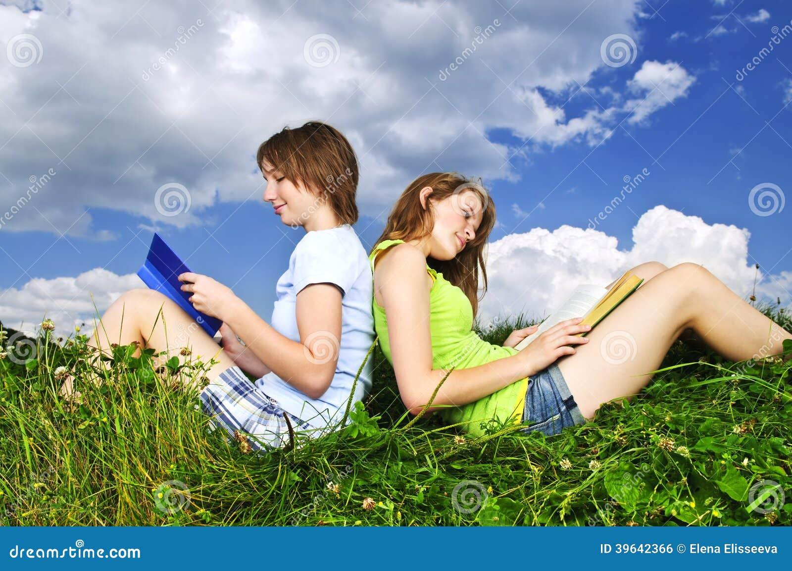 Dos muchachas que leen al aire libre en verano