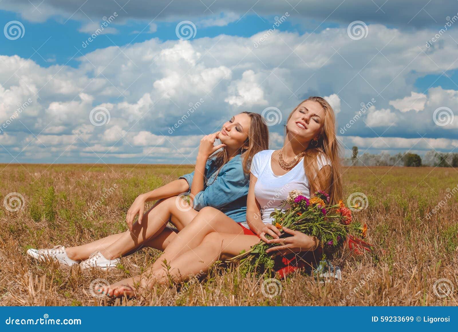 Dos muchachas que se sientan en prado con los wildflowers y