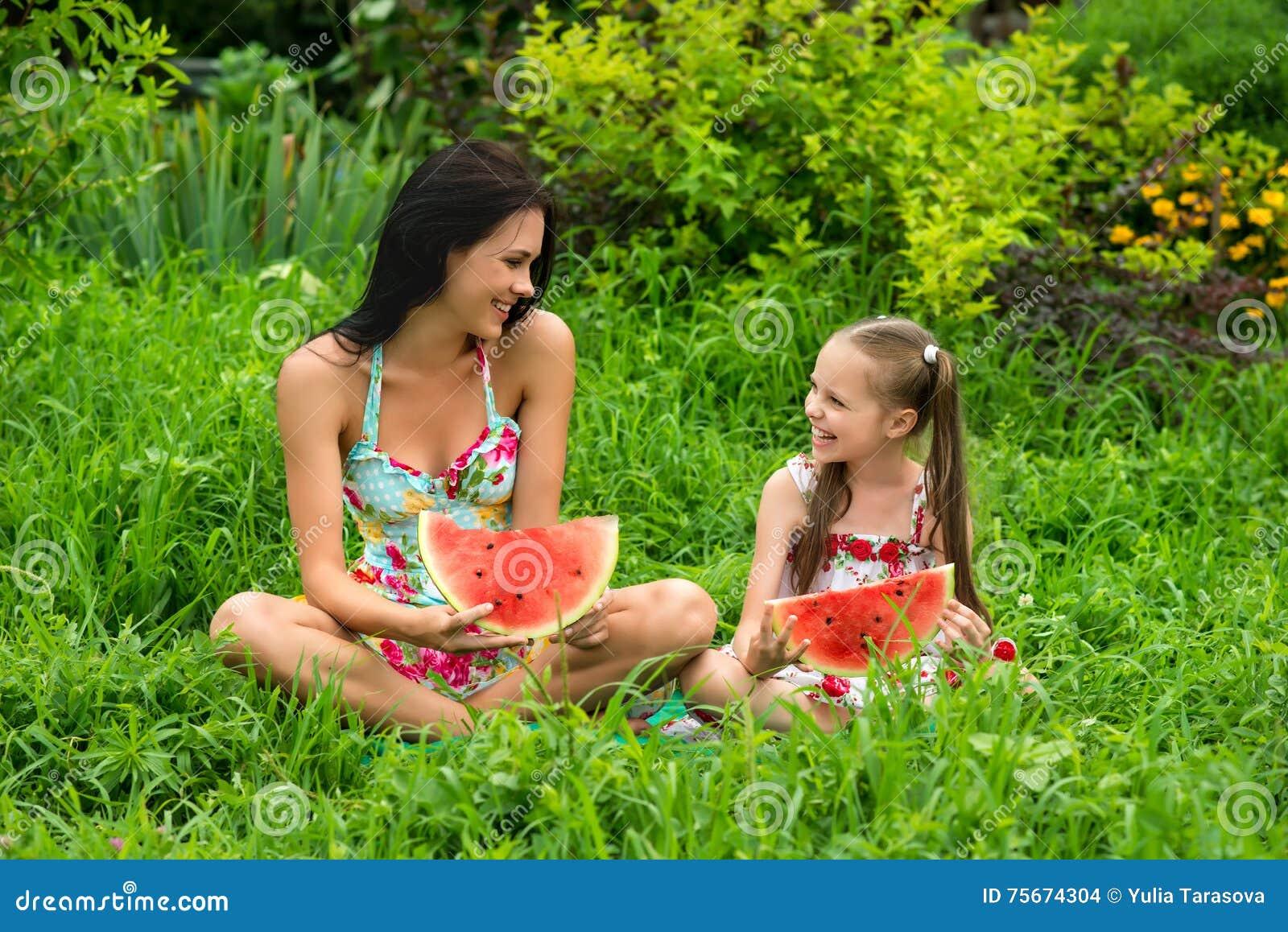 Dos muchachas sonrientes comen la rebanada de sandía al aire libre en la granja