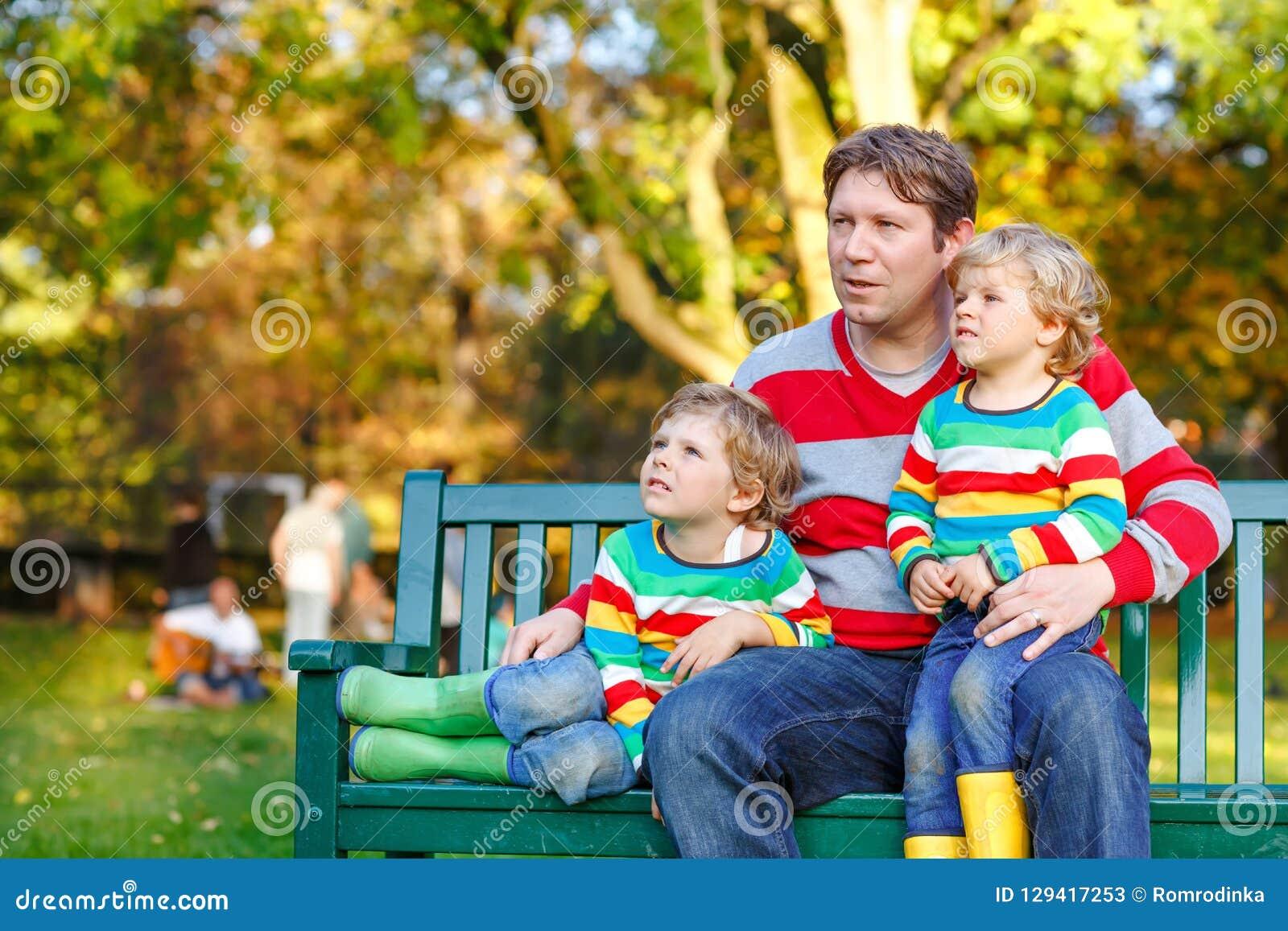 Dos muchachos del niño y padre joven que se sientan junto en ropa colorida en banco Niños sanos lindos, hermanos y