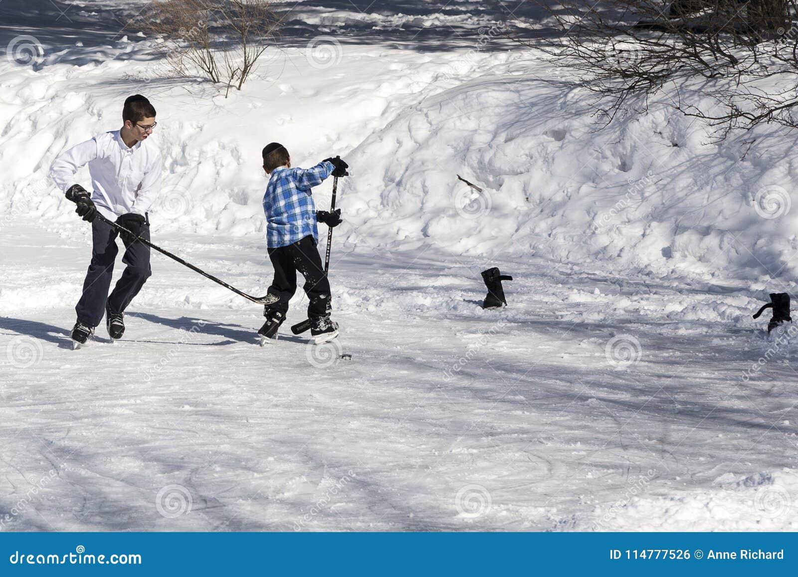 Dos muchachos ortodoxos del judío del hasidim que juegan a hockey en el hielo