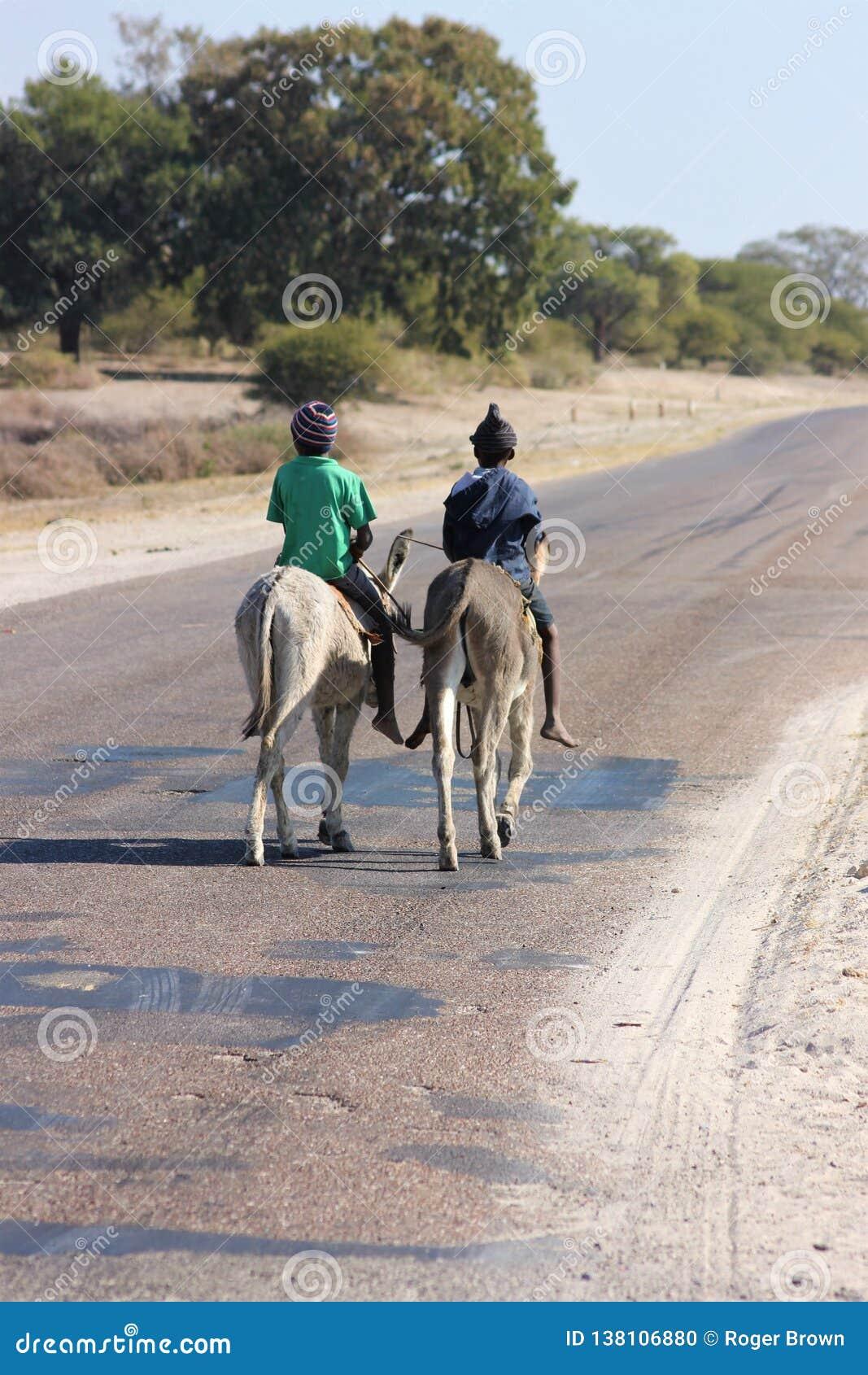 Dos muchachos que montan burros en África