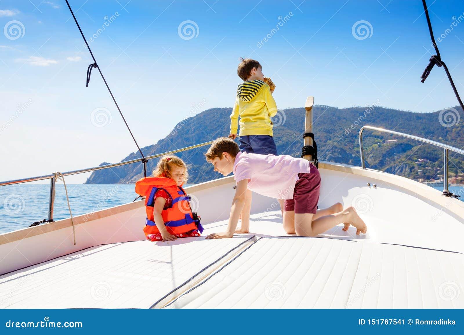 Dos muchachos y niña pequeña del niño que disfrutan de viaje del barco de navegación Vacaciones de familia en el oc?ano o el mar