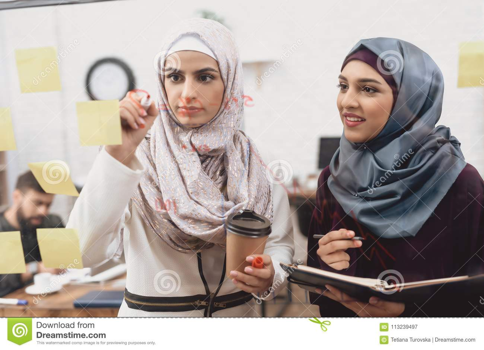 Dos mujeres árabes que trabajan en oficina Los compañeros de trabajo están tomando notas sobre el tablero de cristal