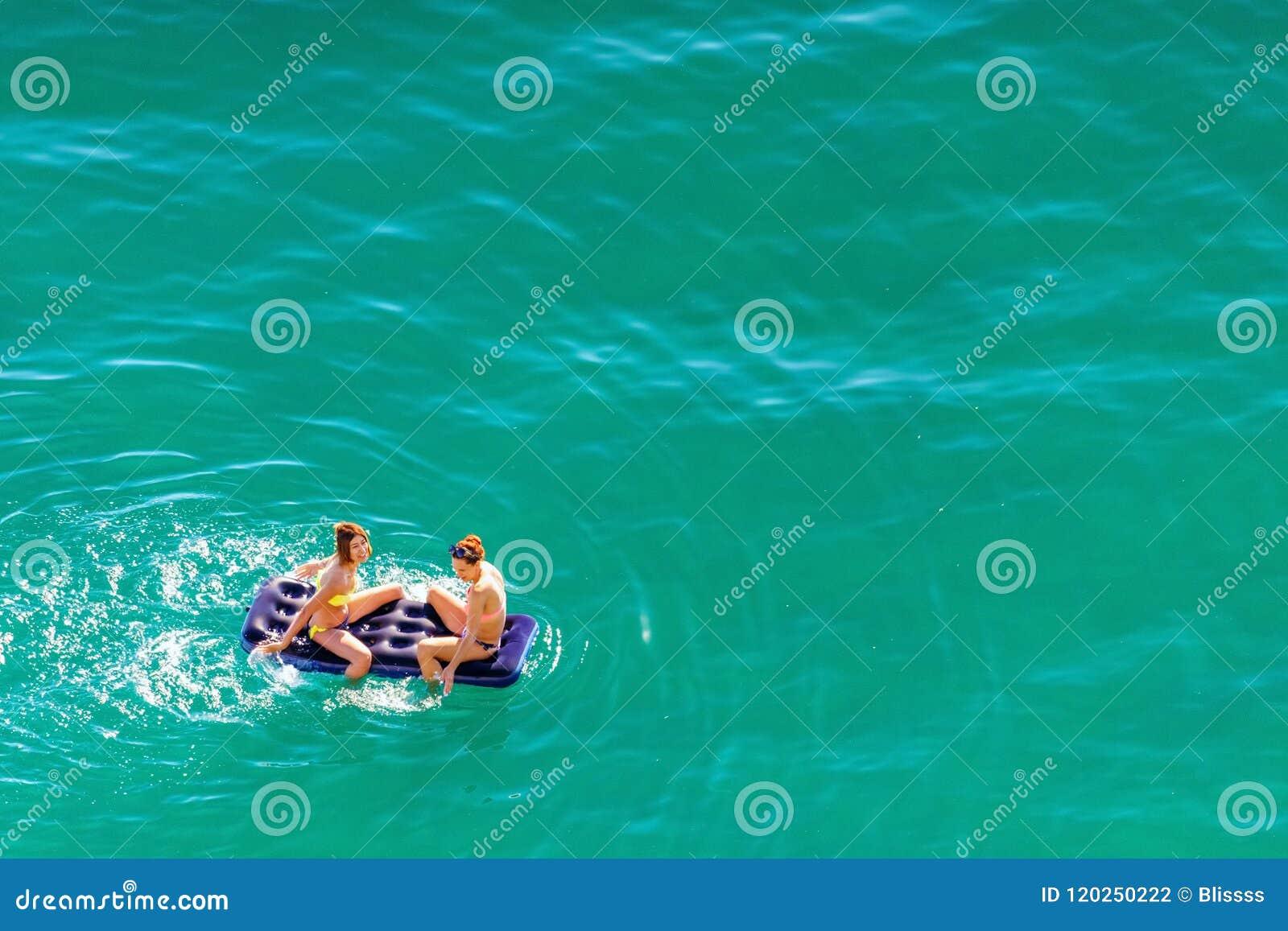 Dos mujeres caucásicas hermosas jovenes en bikini que toman el sol, salpicando y relajándose en el colchón en el agua azul tranqu