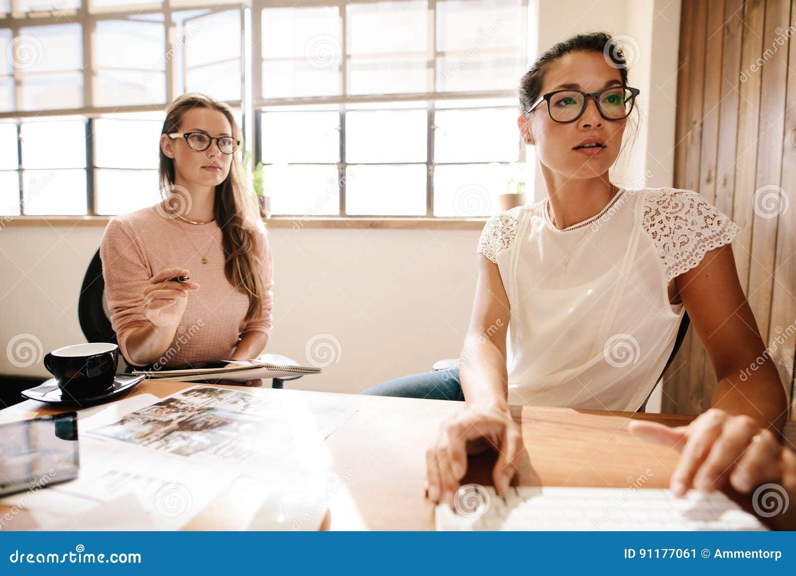 Dos mujeres de negocios que trabajan junto en el escritorio de oficina