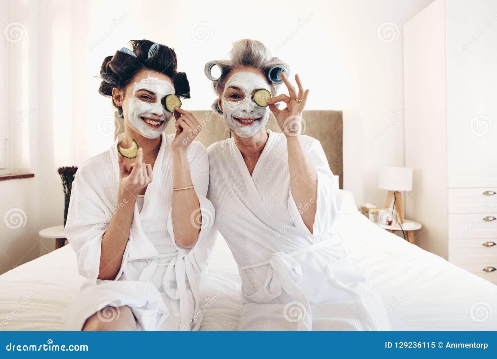 Dos mujeres en albornoces con el paquete de cara de la belleza que se sienta en cama