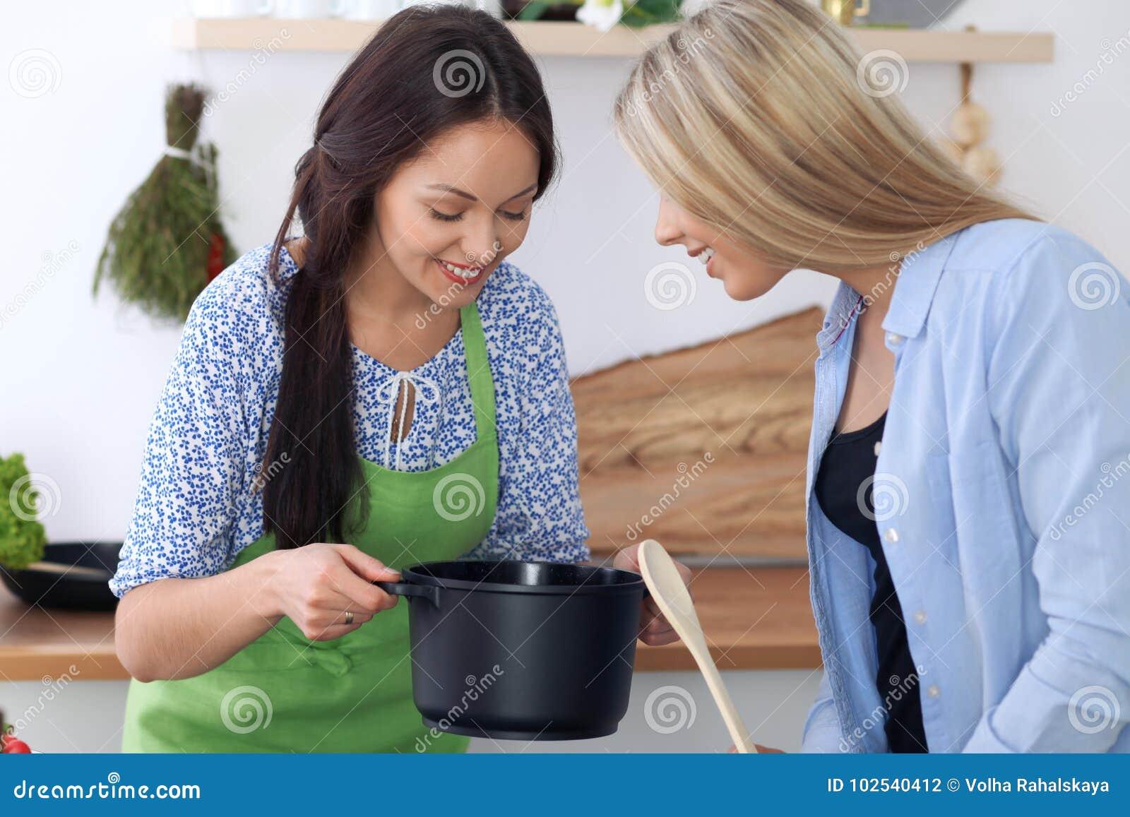 Dos mujeres felices jovenes est n cocinando en la cocina for Cocinando para los amigos