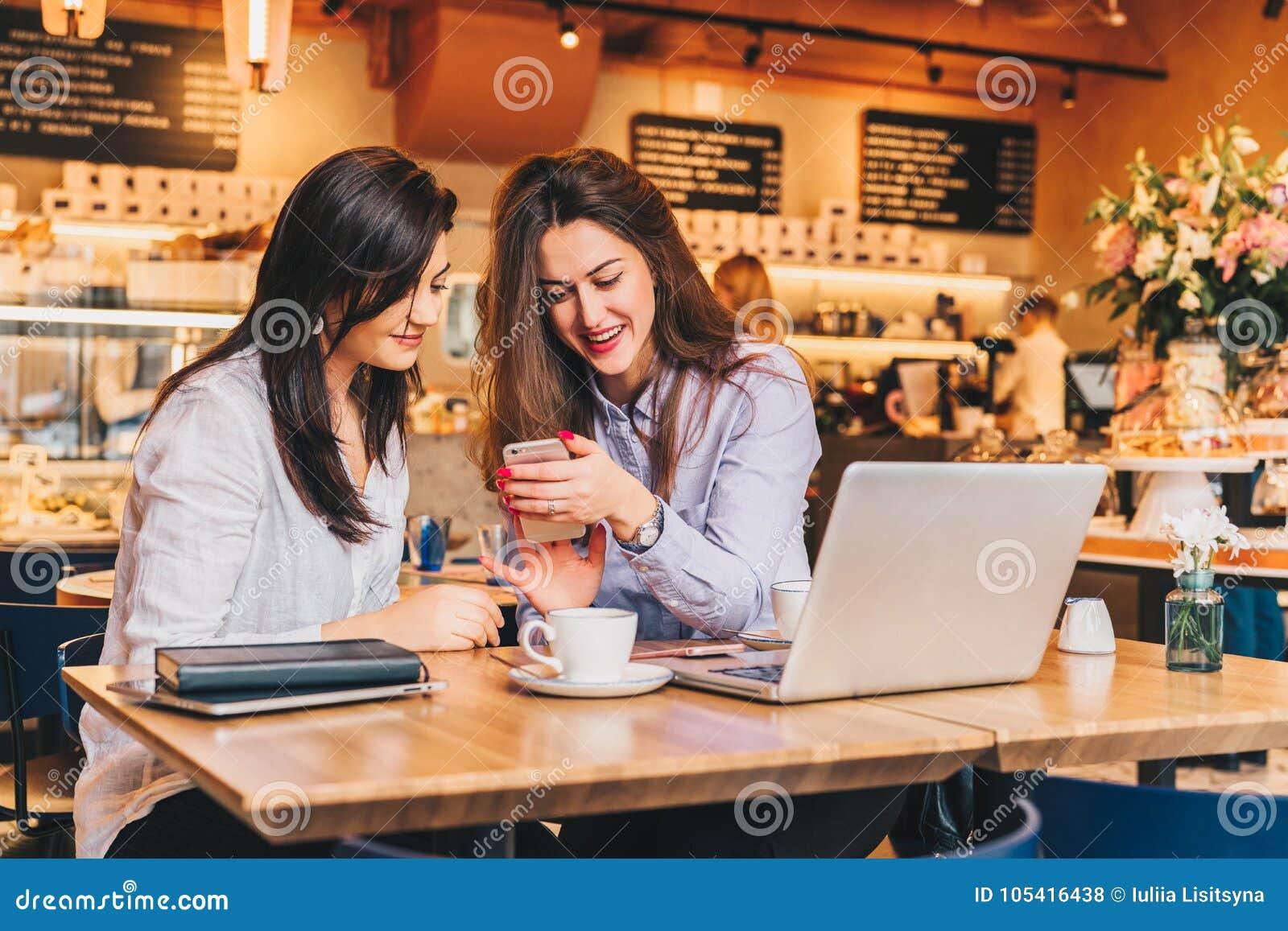 Dos mujeres felices jovenes se están sentando en café en la tabla delante del ordenador portátil, usando smartphone y la risa