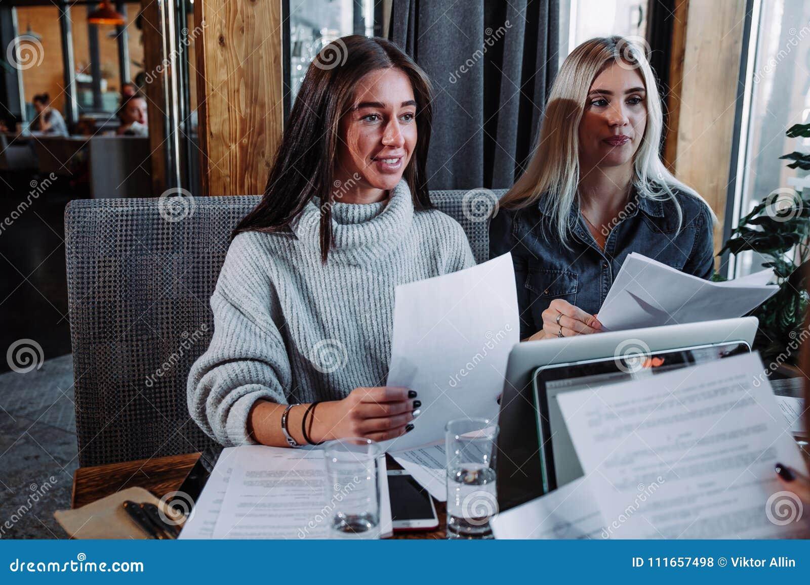 Dos mujeres hermosas jovenes en una reunión de negocios en un café