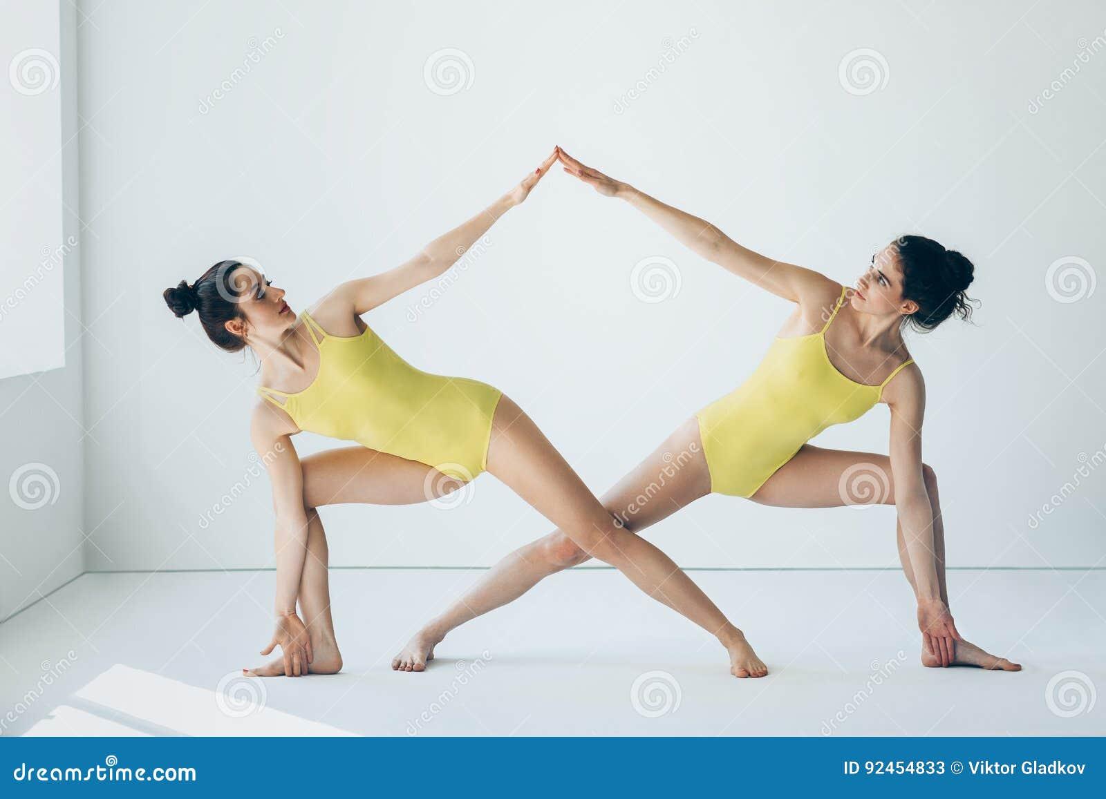 Dos mujeres hermosas que hacían asana de la yoga ampliaron actitud del ángulo lateral