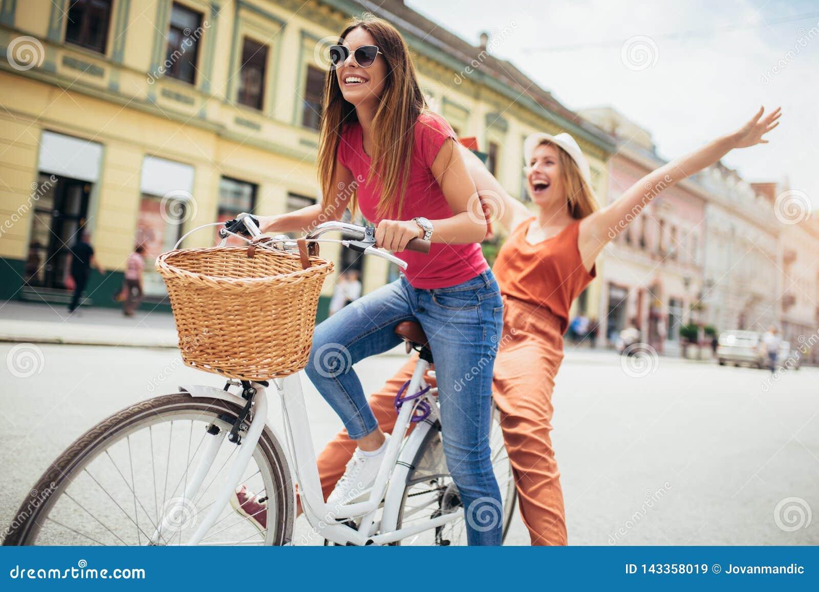Dos mujeres hermosas que hacen compras en la bici en la ciudad