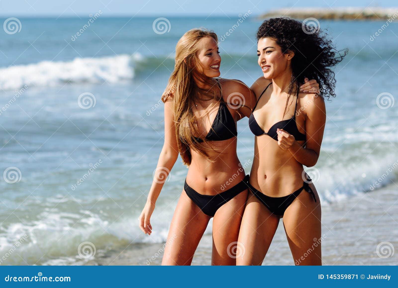 Dos mujeres jovenes con los cuerpos hermosos en traje de ba?o en una playa tropical