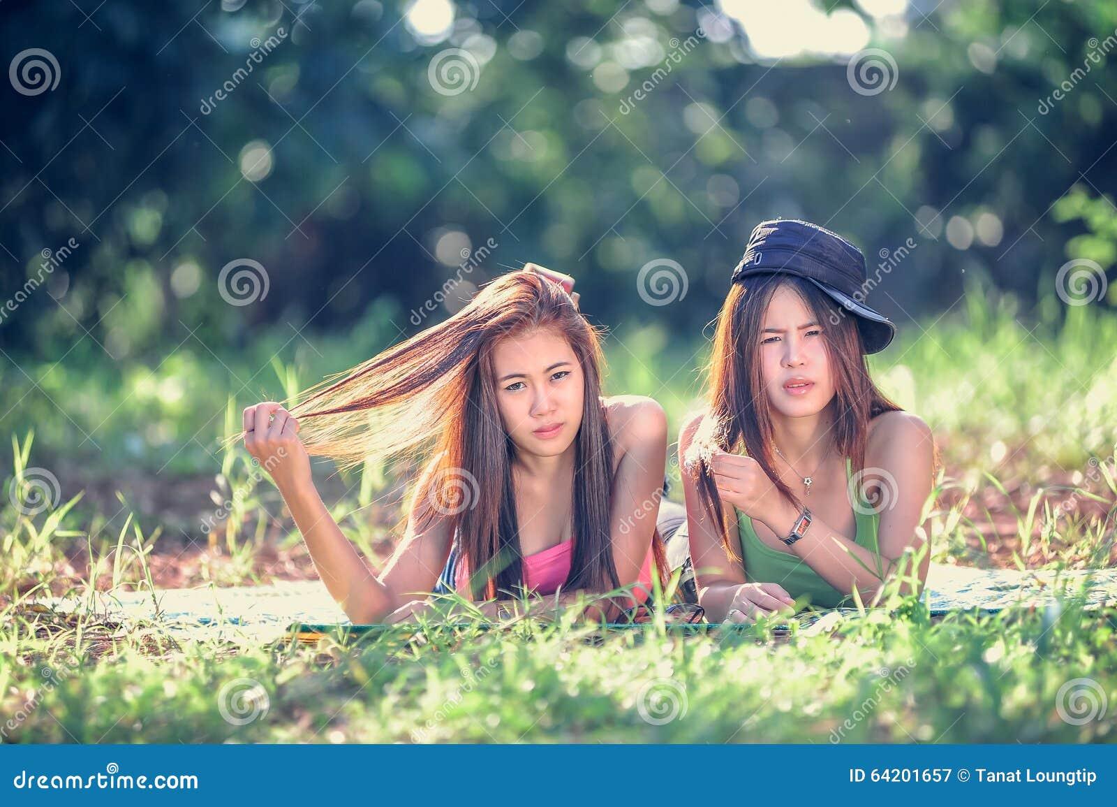 Dos mujeres jovenes de Asia que mienten en hierba