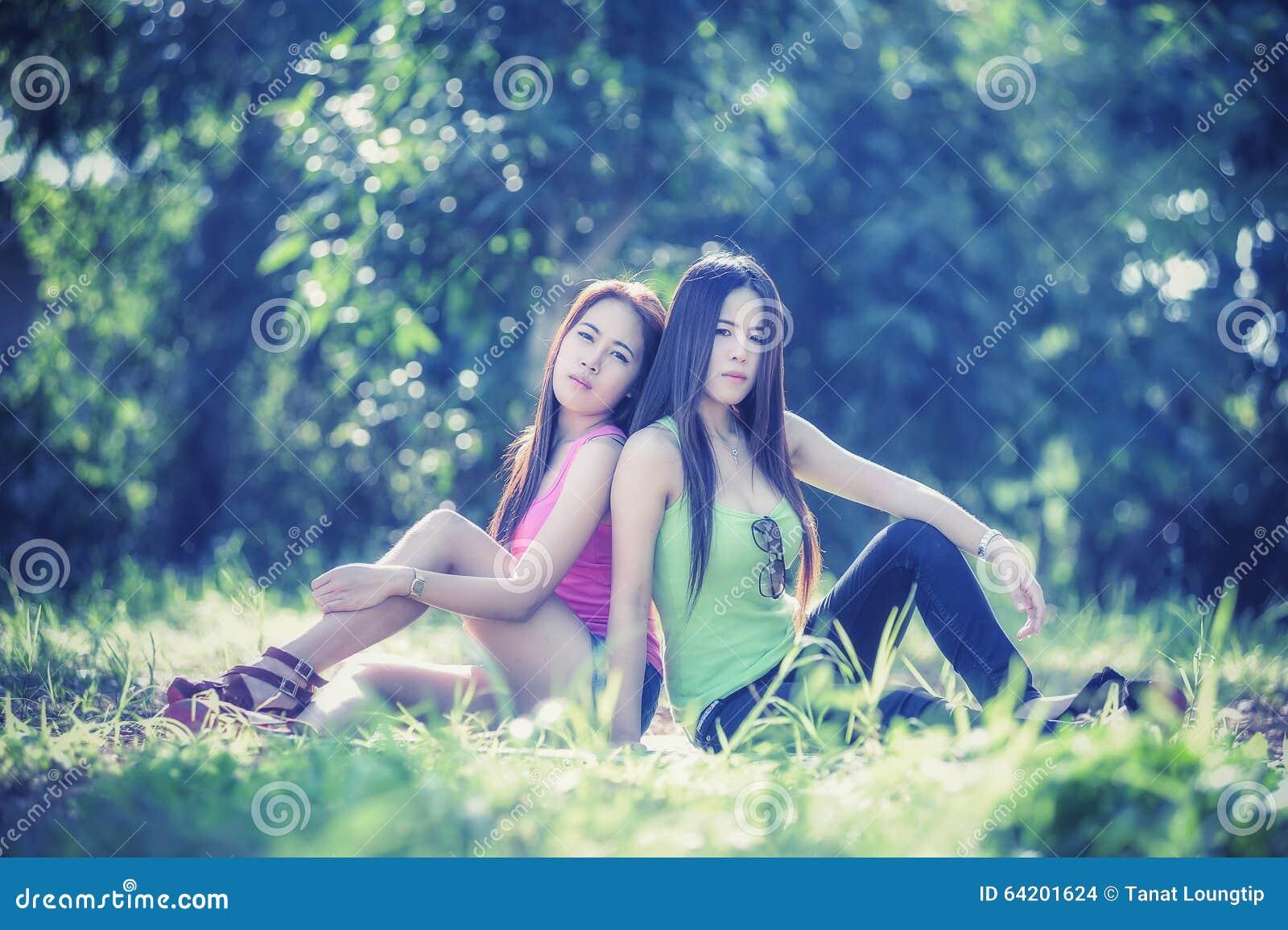 Dos mujeres jovenes de Asia que se sientan en hierba