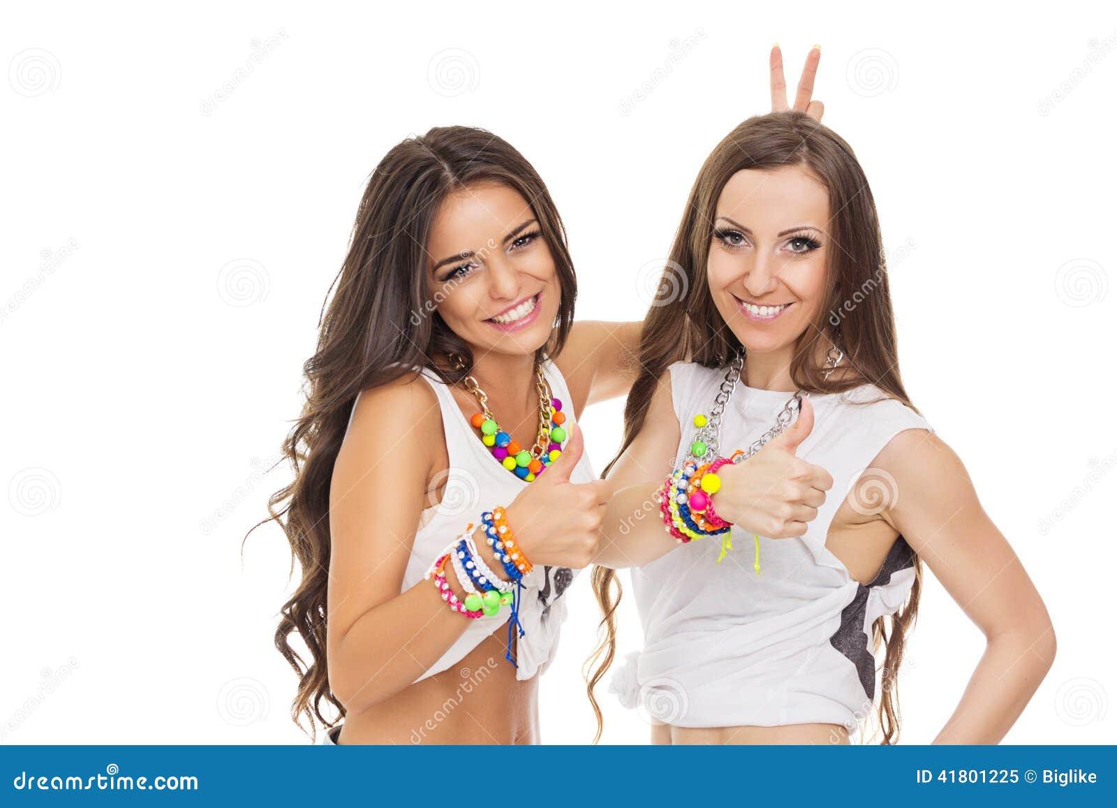 Dos mujeres jovenes de moda felices que muestran los pulgares para arriba que llevan la joyería colorida