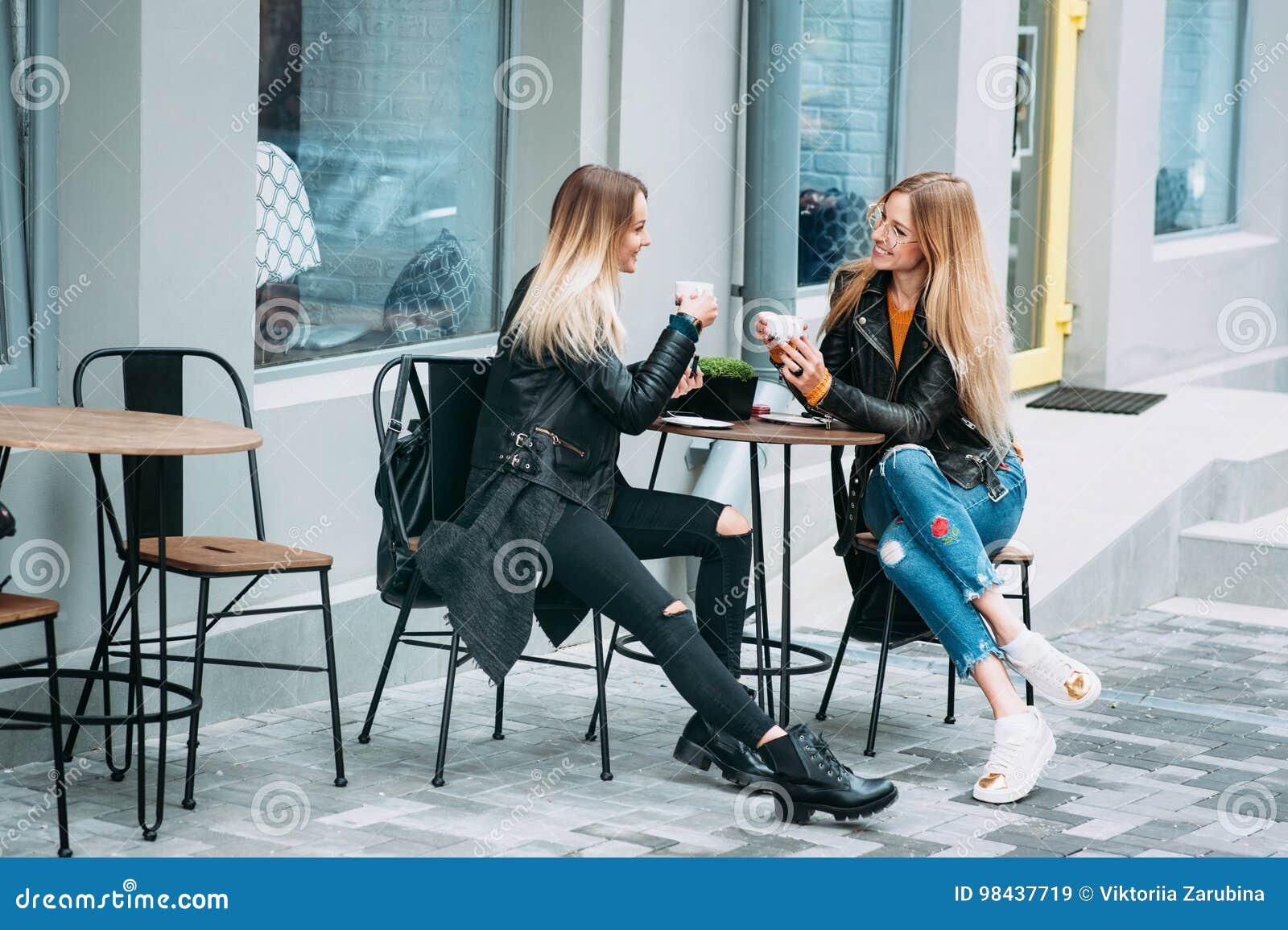 Dos mujeres jovenes hermosas que beben té y que cotillean en el restaurante agradable al aire libre