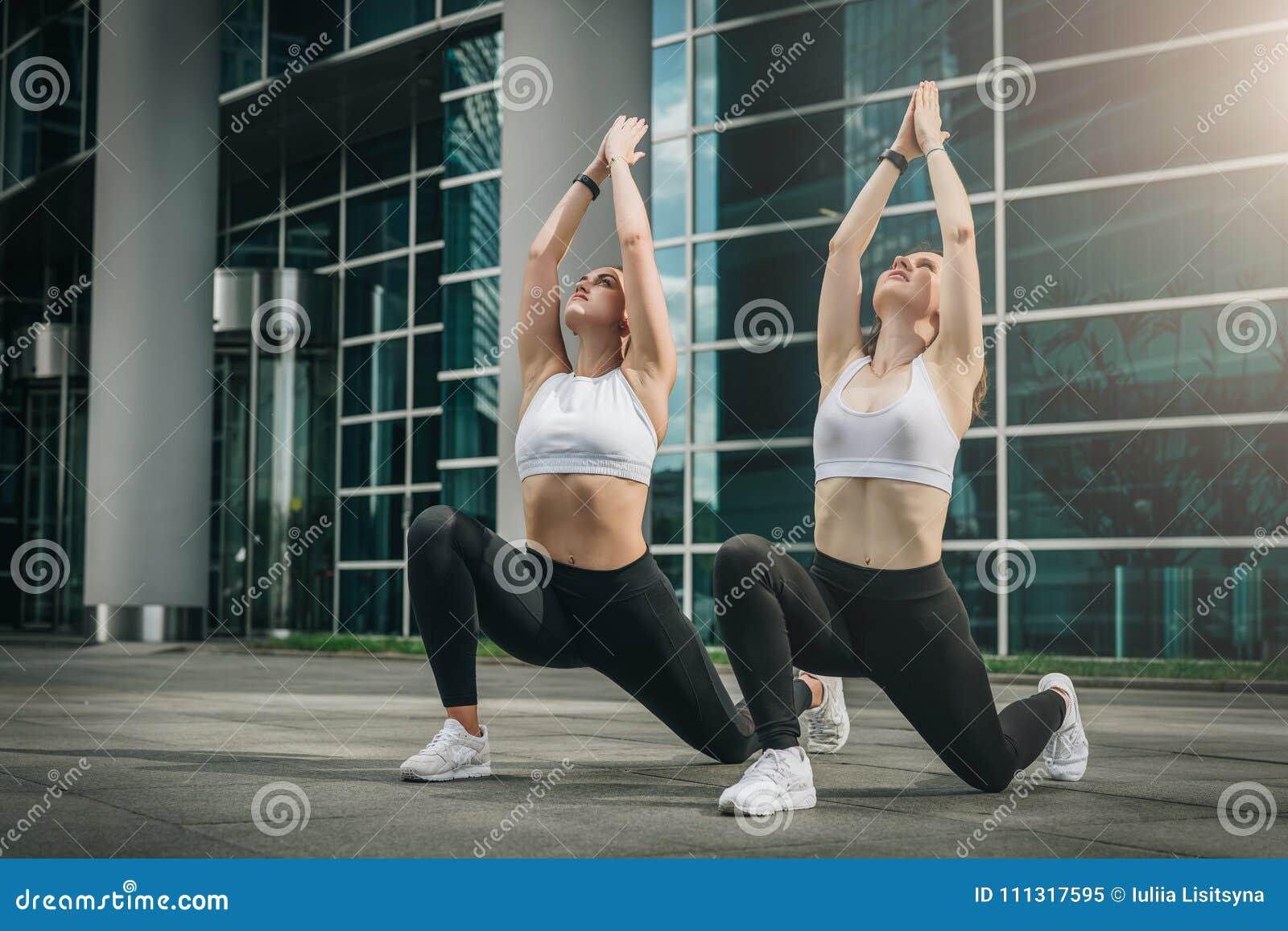 Dos mujeres jovenes, muchachas que hacen estirando los ejercicios, calentamiento, haciendo yoga en la calle de la ciudad Entrenam