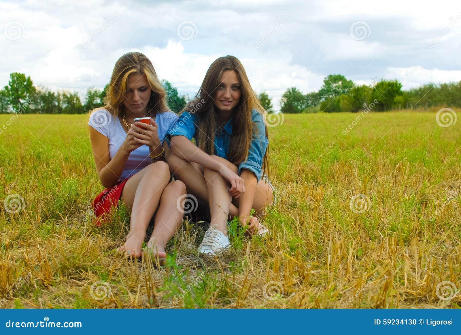Dos mujeres jovenes que se sientan en la sonrisa del prado del verano