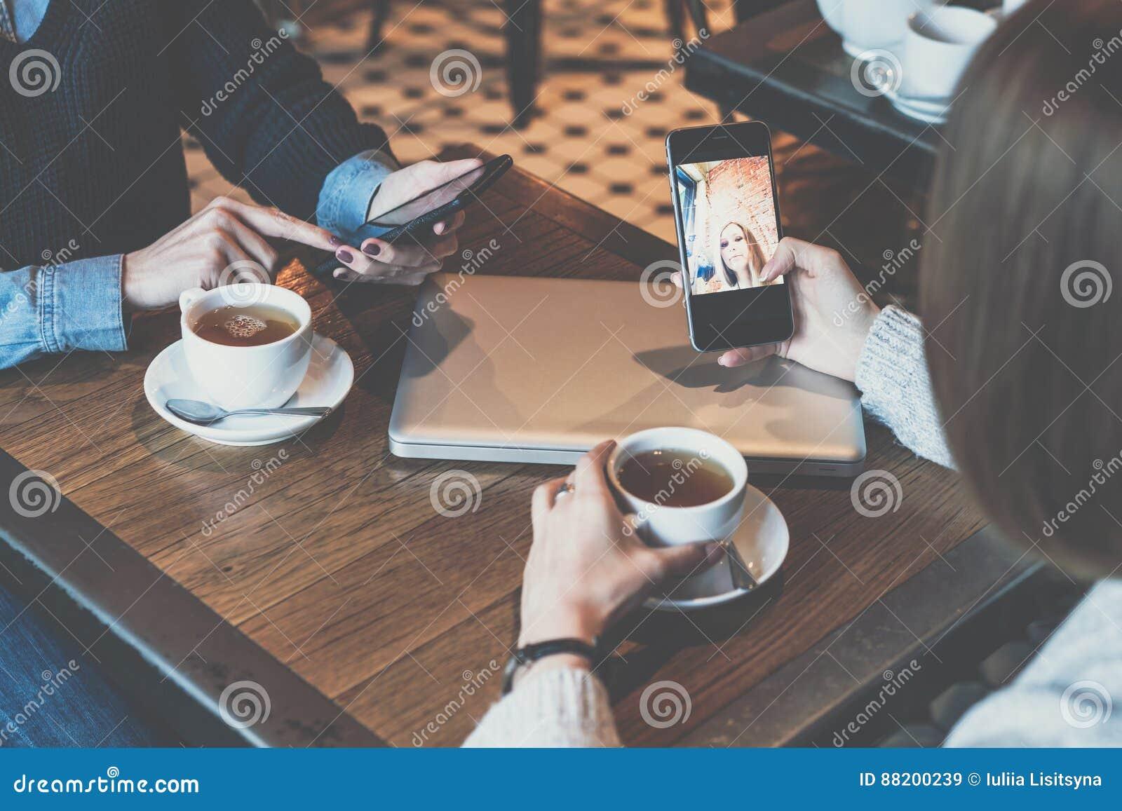 Dos mujeres jovenes que se sientan en la tabla en café y que usan smartphones Muchachas que hacen compras en línea