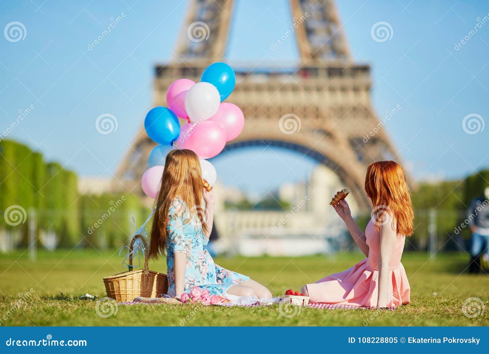 Dos mujeres jovenes que tienen comida campestre cerca de la torre Eiffel en París, Francia