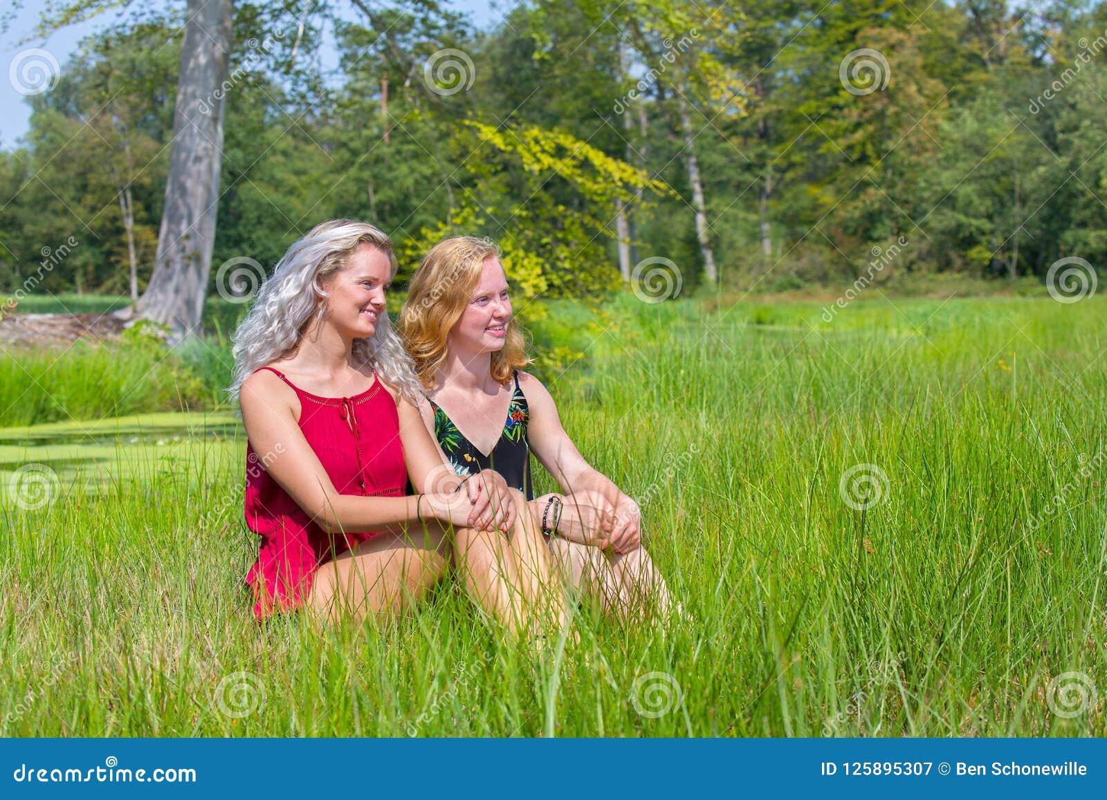 Dos mujeres jovenes se sientan juntas en naturaleza