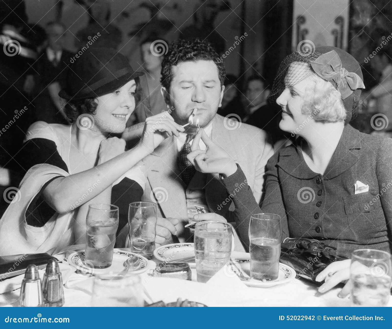 Dos mujeres que encienden un cigarrillo para un hombre (todas las personas representadas no son vivas más largo y ningún estado e