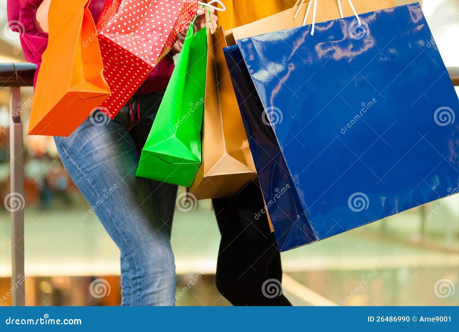 Dos mujeres que hacen compras con los bolsos en alameda