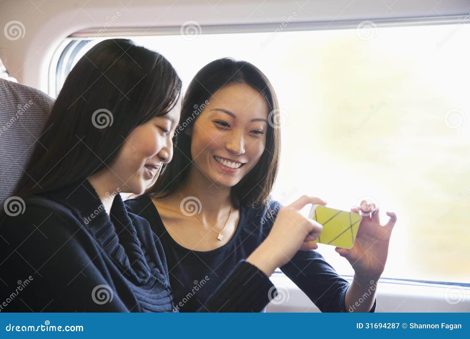 Dos mujeres que miran el teléfono móvil en un tren