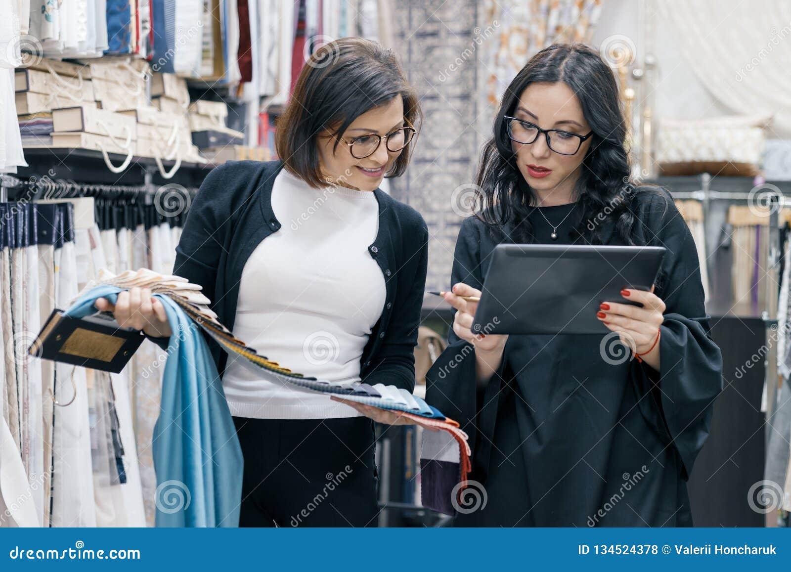 Dos mujeres que trabajan con la tableta digital de las telas interiores en la sala de exposición para las cortinas y las telas de