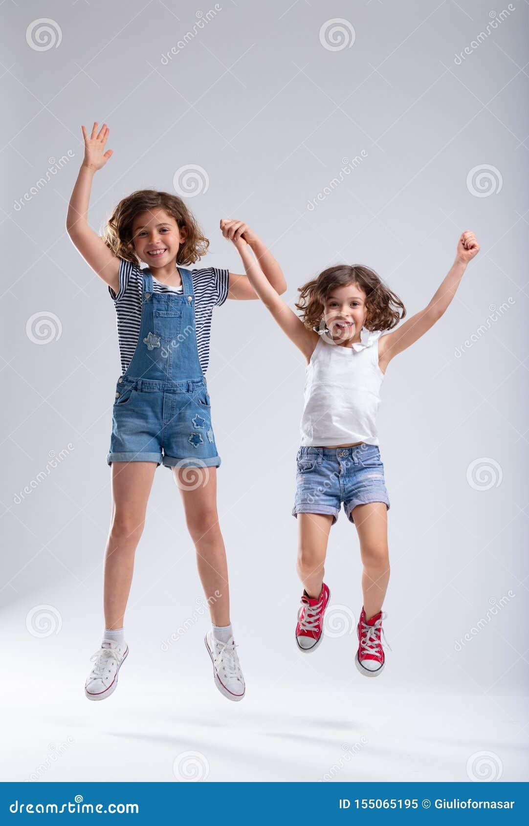 Dos niñas animadas vivaces que saltan junto
