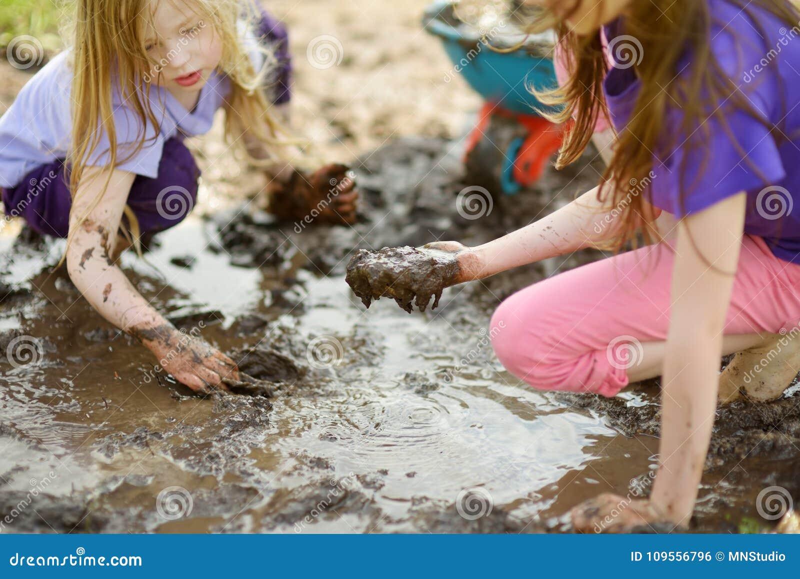 Dos niñas divertidas que juegan en un charco de fango mojado grande en día de verano soleado Niños que consiguen sucios mientras