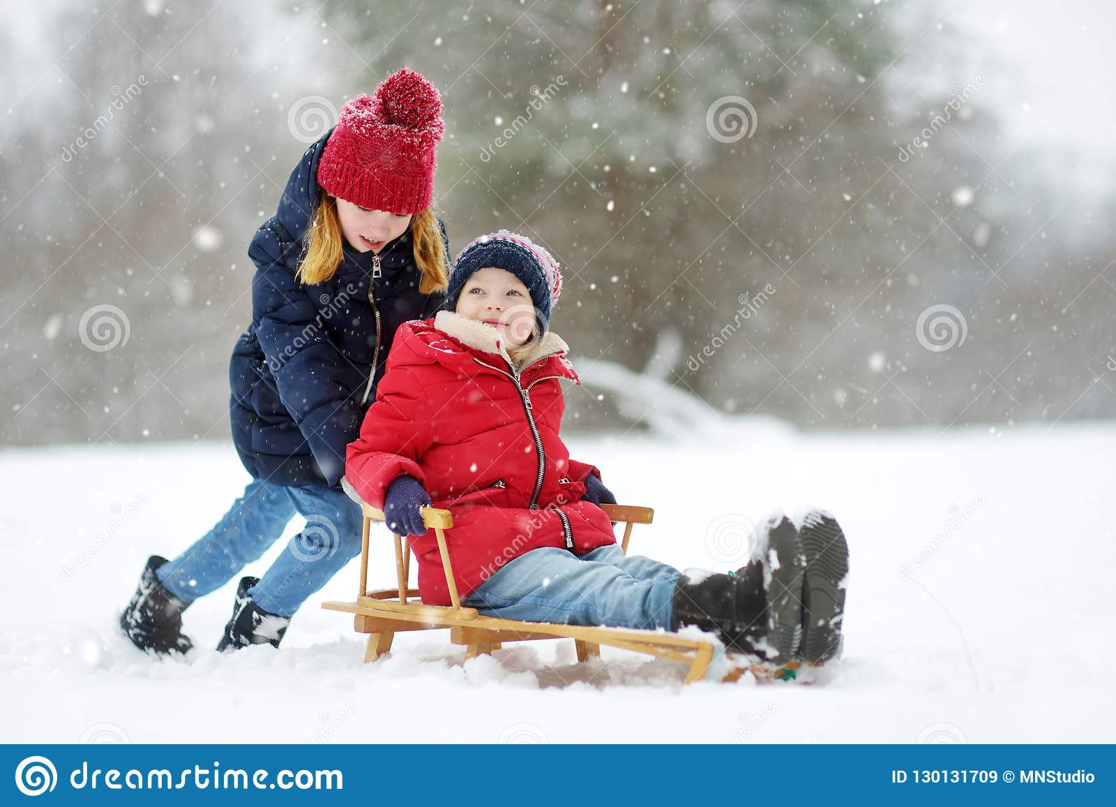 Dos niñas divertidas que se divierten con un trineo en parque hermoso del invierno Niños lindos que juegan en una nieve
