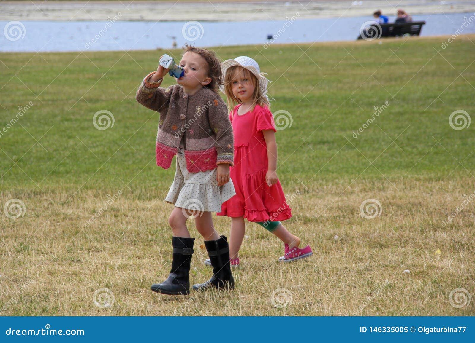 Dos niñas elegantes hermosas están caminando en el parque del StJames