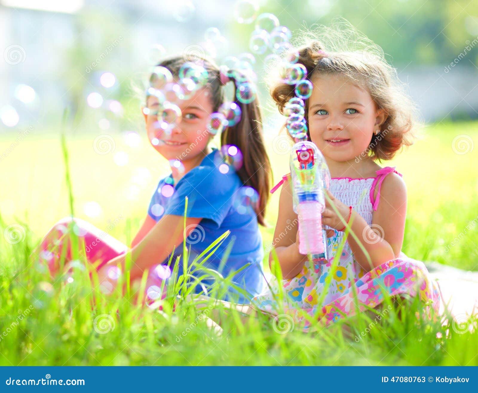 Dos niñas están soplando burbujas de jabón