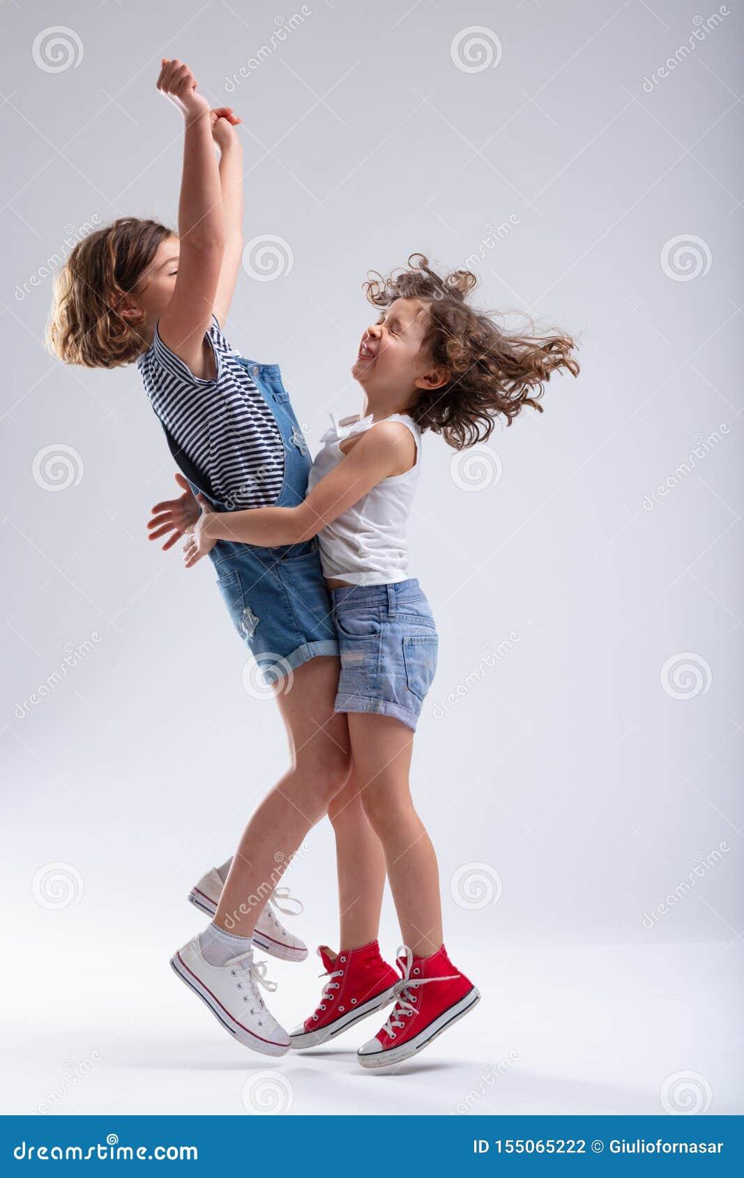 Dos niñas felices que abrazan y que saltan