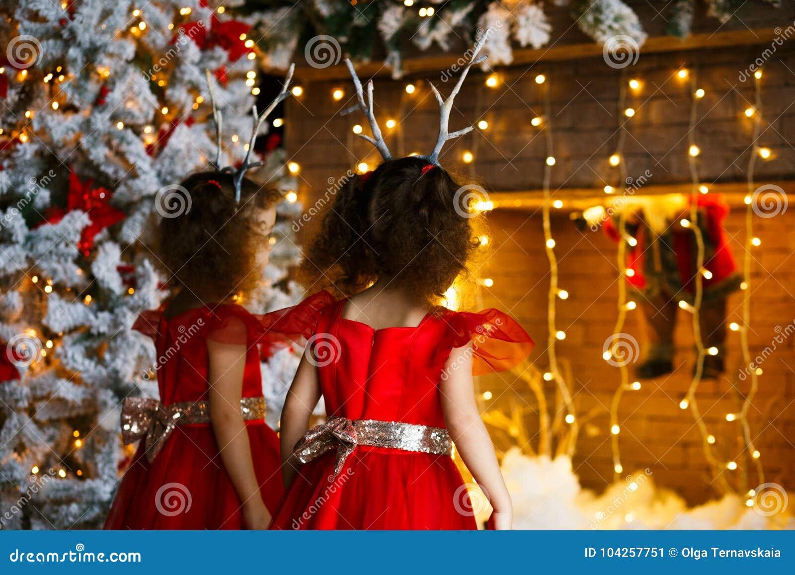 Dos niñas rizadas que miran la chimenea de la Navidad cerca del árbol de navidad hermoso Gemelos en los vestidos rojos que miran