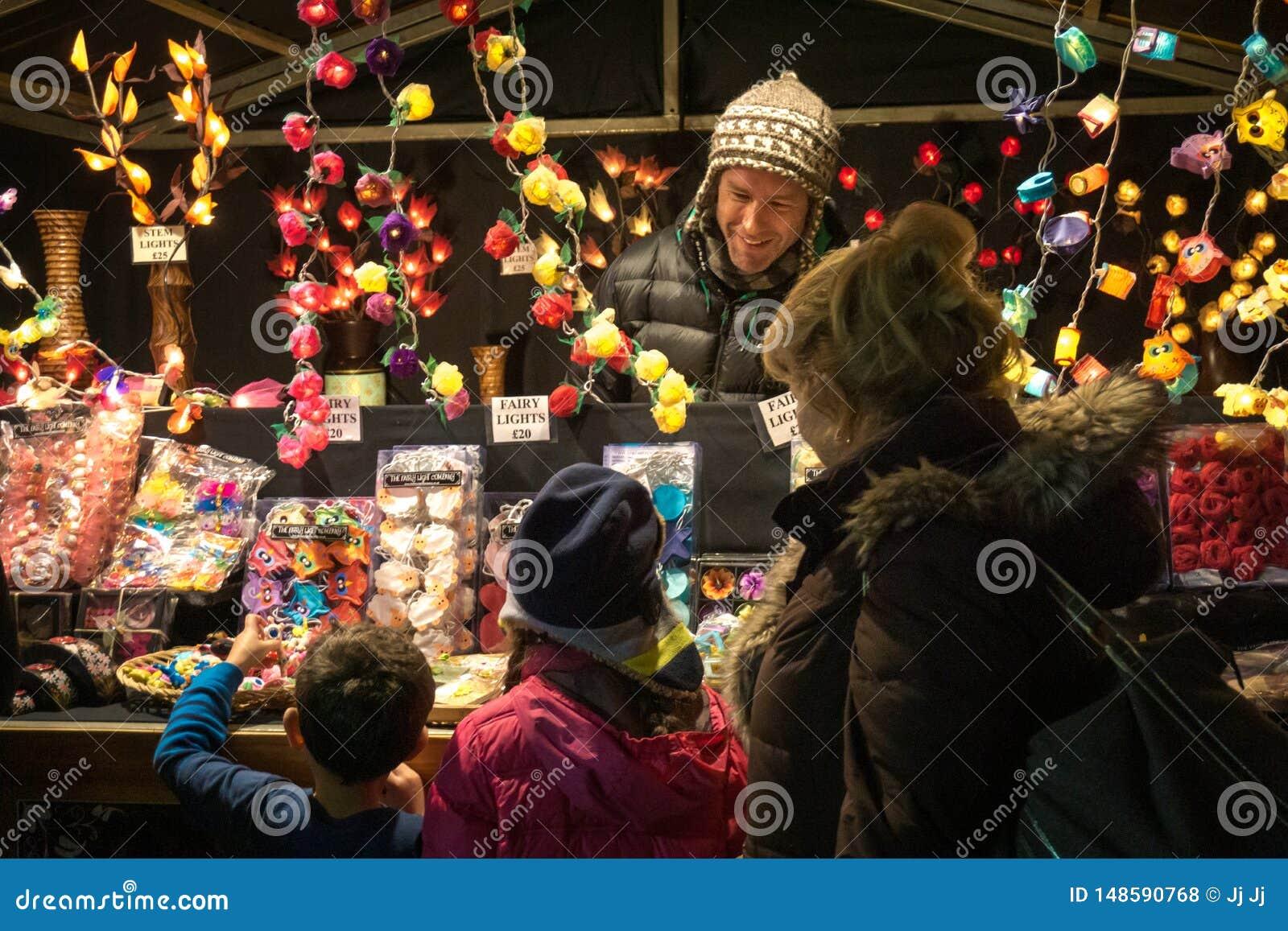 Dos ni?os emocionados con su abuela en un mercado de la Navidad