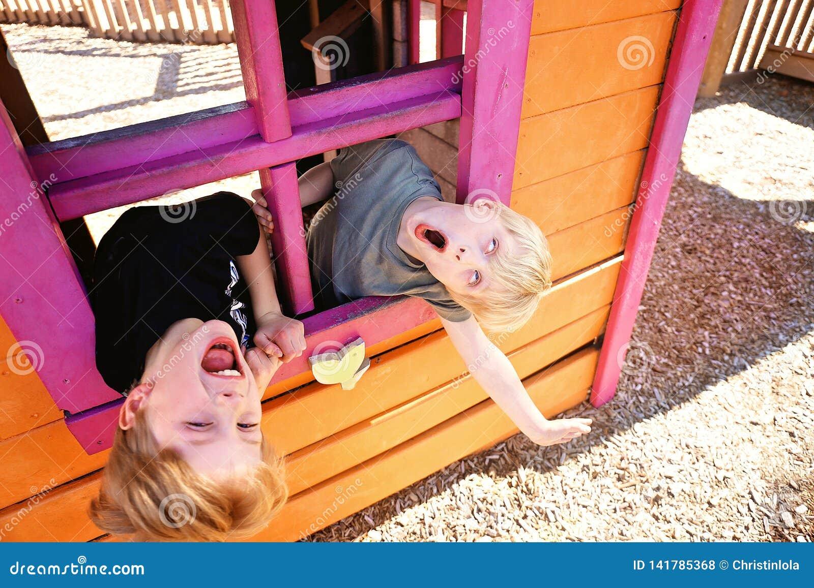 Dos niños lindos que juegan afuera en una casa del club en un patio, haciendo caras divertidas