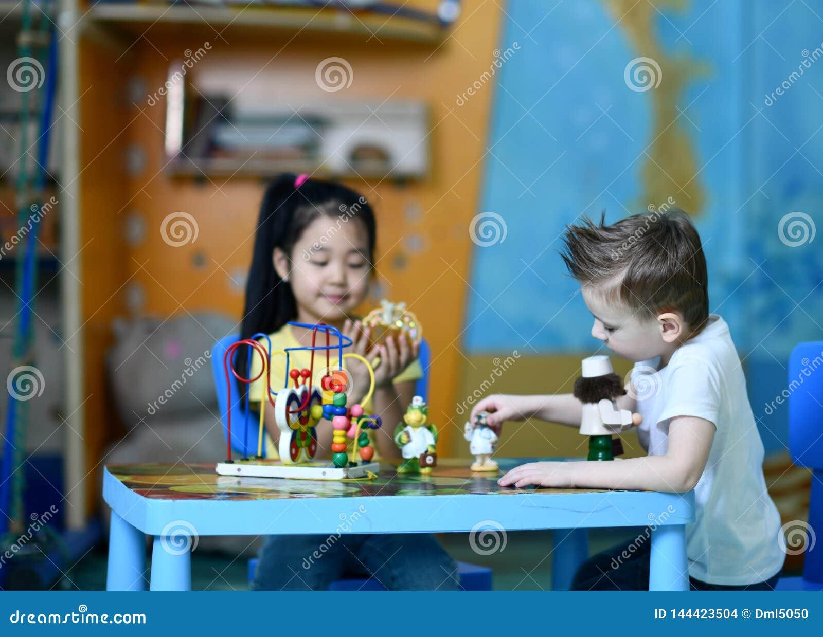 Dos ni?os muchacho y juego de la muchacha entusiasta en los doctores del juguete de la tabla