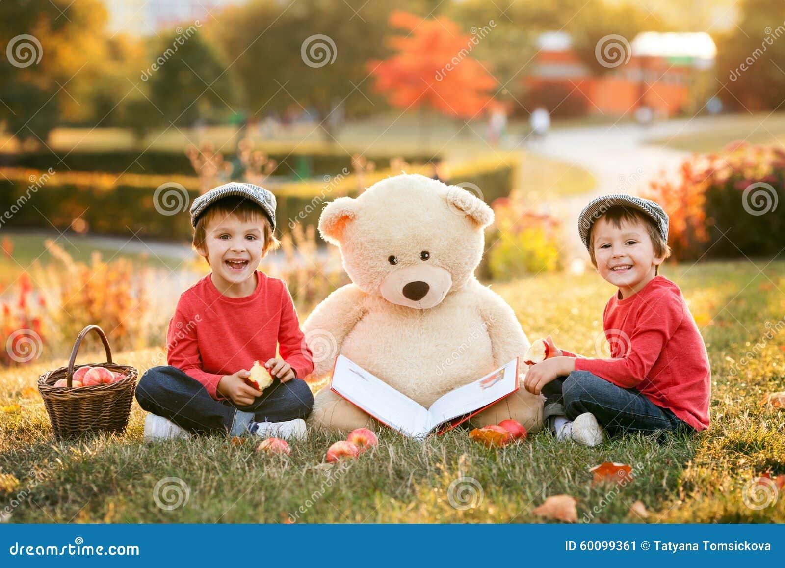 Dos niños pequeños adorables con su amigo del oso de peluche en el parque