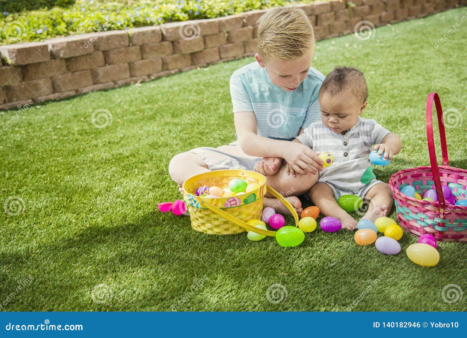 Dos niños pequeños lindos que recogen los huevos en una caza del huevo de Pascua al aire libre