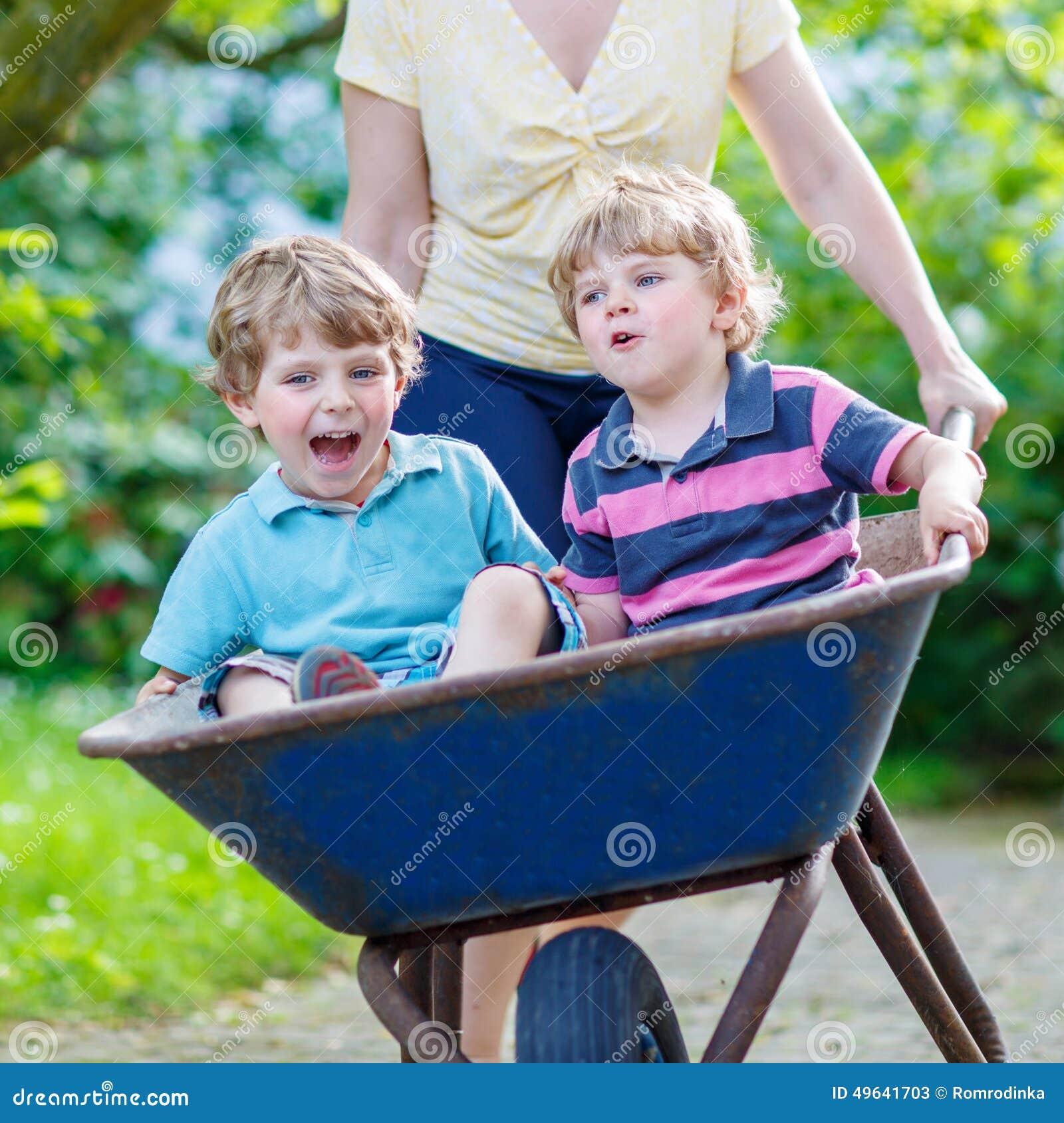 Dos niños pequeños que se divierten en una carretilla que empuja por la madre