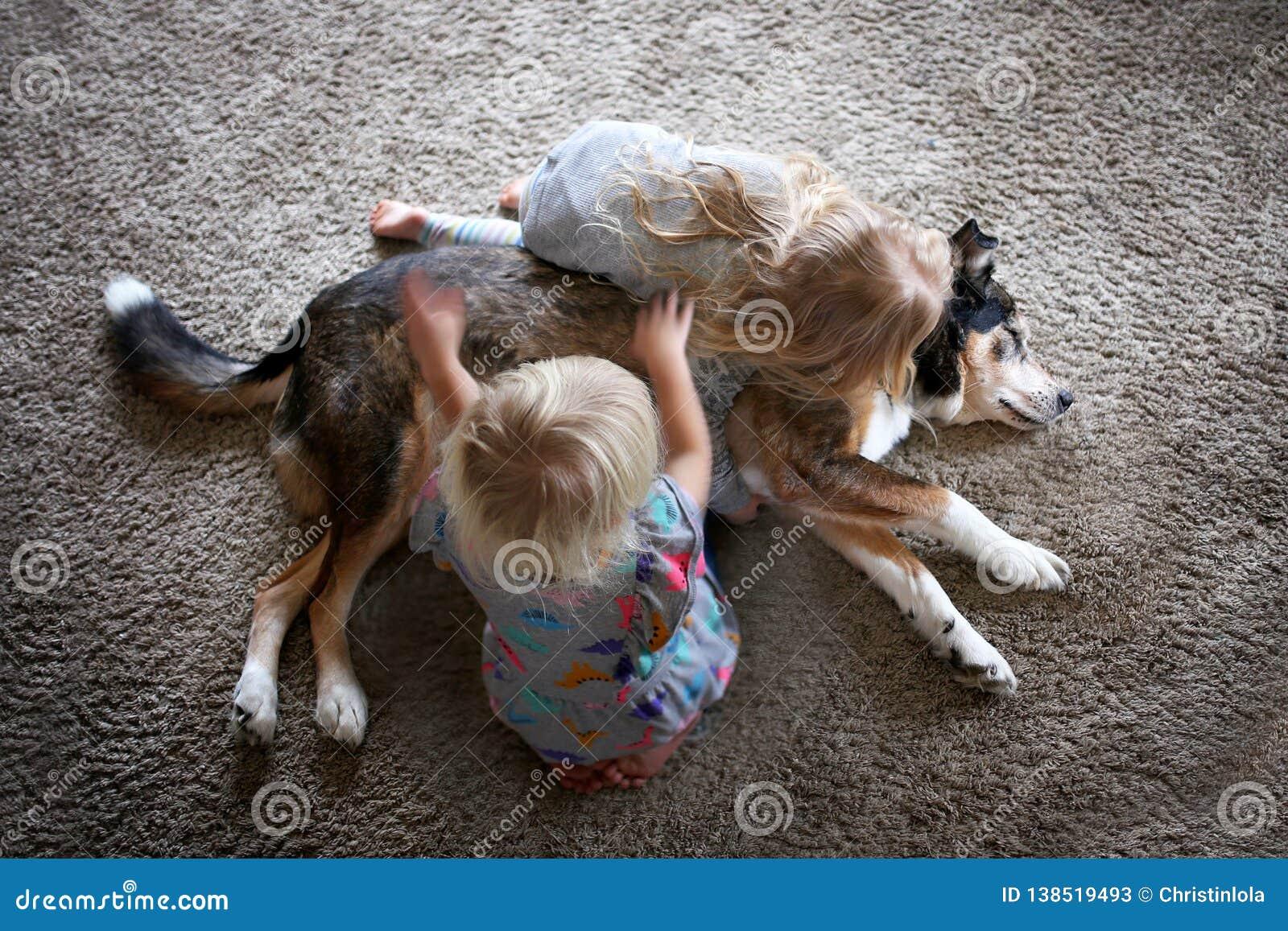 Dos niños que abrazan y que acarician su perro casero