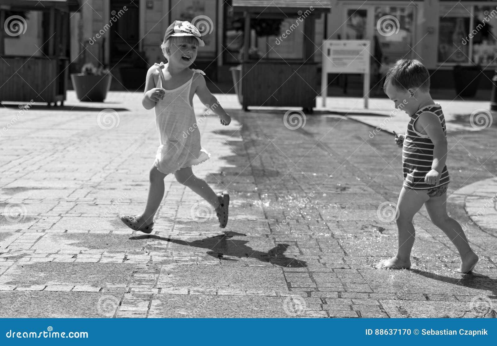 Dos niños que juegan con agua en cuadrado de ciudad pavimentado