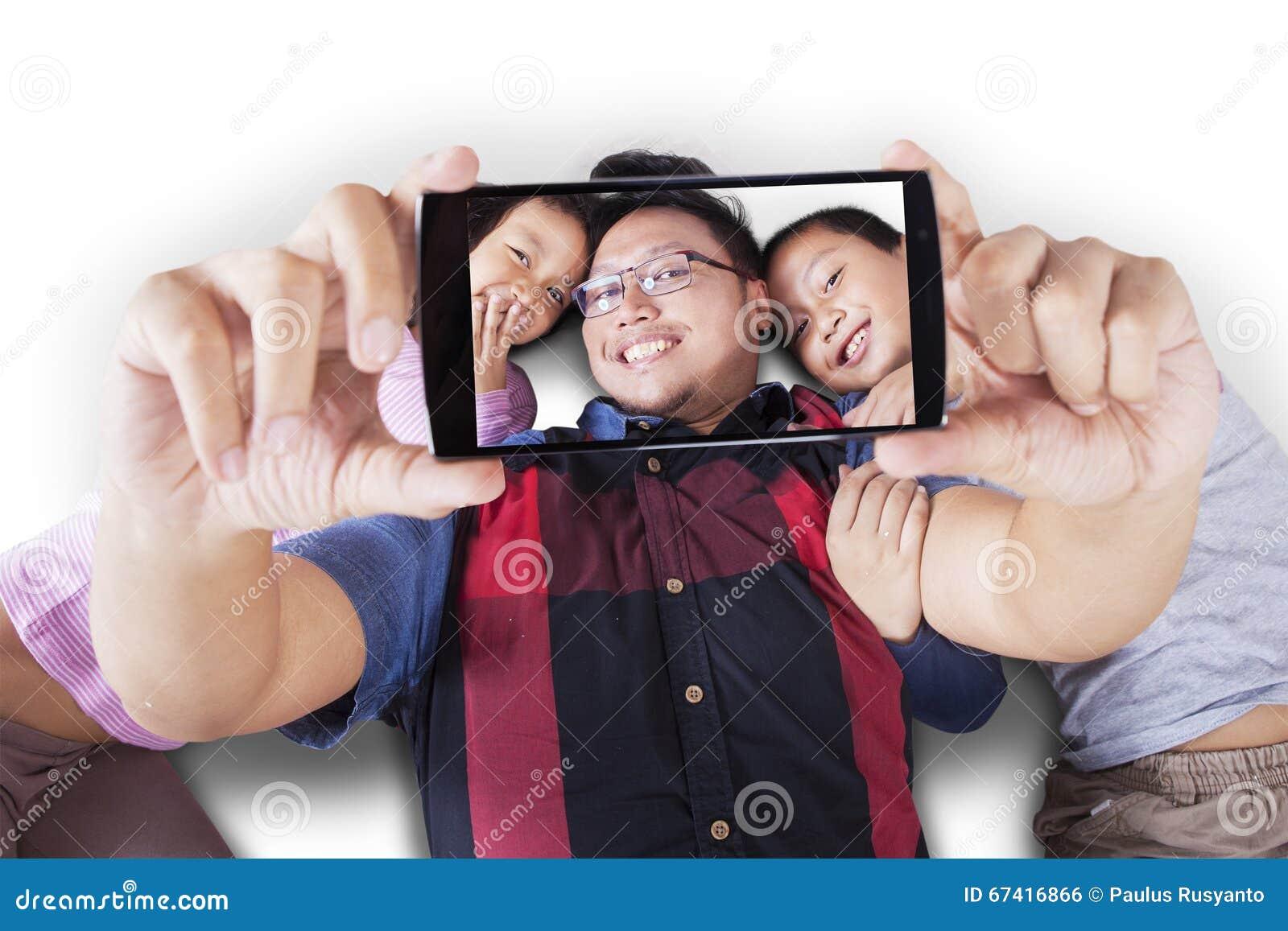 Dos niños y padre que toman el selfie junto